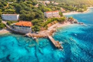 Aerial view with sea coast, sandy beach, blue water, hotels